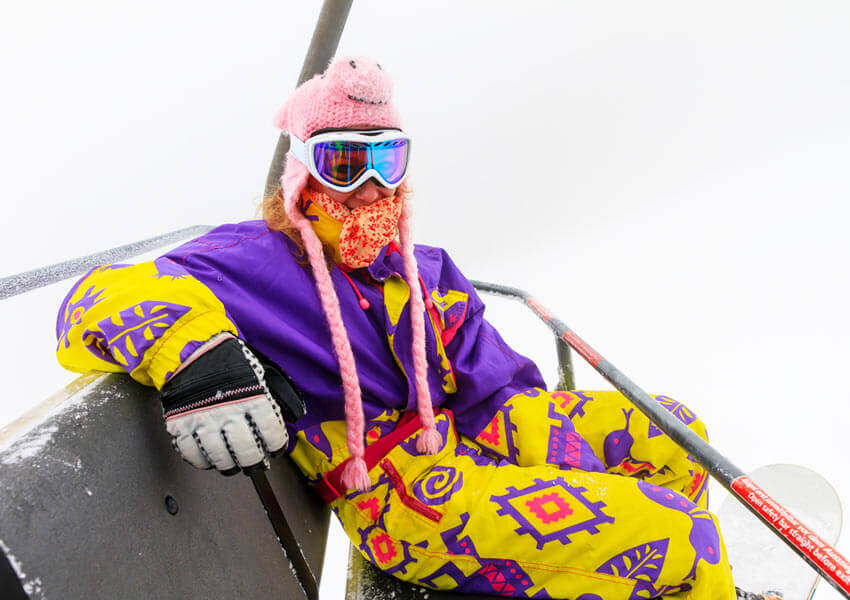 skier on ski lift in bright outfit